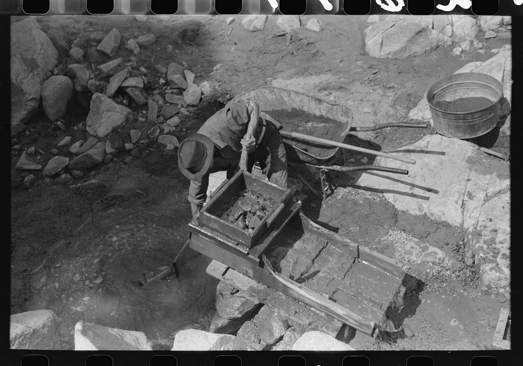 """Eugene Davis, gold prospector, operating """"rocker"""". Rocks and sticks remain in the screened box at the top when water is sluiced over them and the contraption is rocked by the handle. Loose dirt and any mineral content washes below, the dirt gradually washing through and the heavy gold and minerals settling to the bottom and behind the ridges. Pinos Altos, New Mexico"""