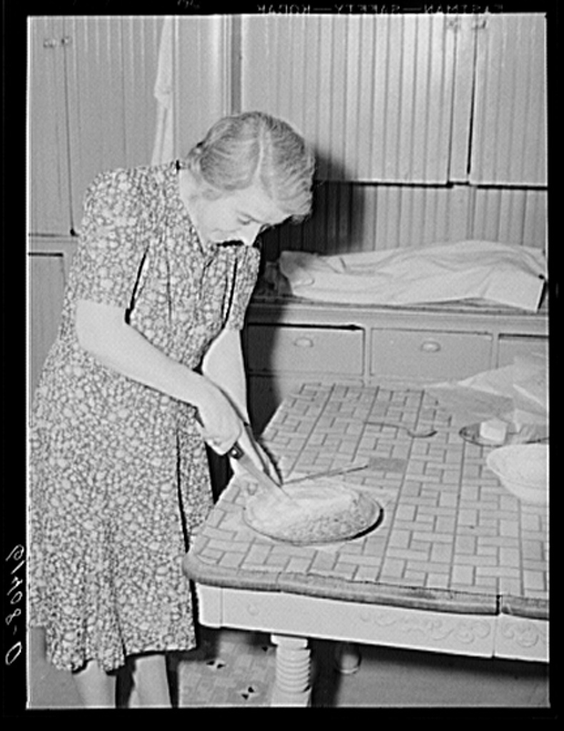 Farm woman cutting pieces of pie for supper. Meeker County, Minnesota