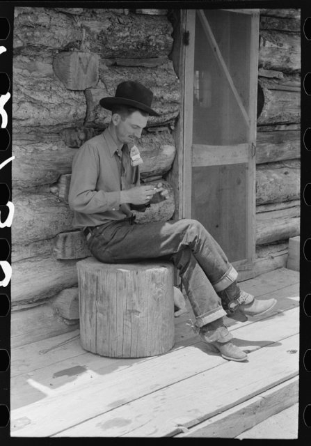 Farmer rolling a cigarette. Construction of log house is shown. This farmer rents farm and house from the man who homesteaded the place but is now unable to farm. Pie Town, New Mexico