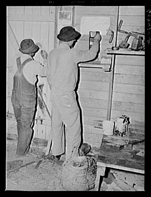 Farmers putting in time slips at end of day. Deshee Unit, Wabash Farms, Indiana. All the land here is farmed cooperatively and profits are distributed according to amount of work done