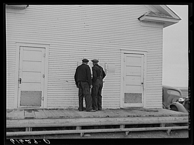 Farmers reading ballots posted outside schoolhouse. Election day, McIntosh County, North Dakota