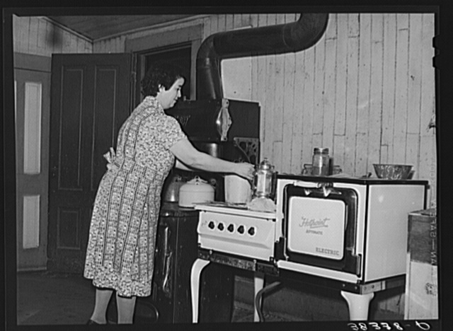 Farmer's wife in her kitchen near Auburn, California. Notice the electric stove and wood or coal range adjoining. This is a common sight in this section which is generally electrified but where electricity rates are higher than many farmers can afford to pay. Placer County, California