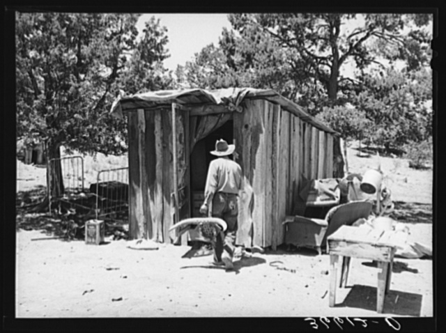 Faro Caudill taking household articles into shed for storage while he moves his dugout. Pie Town, New Mexico