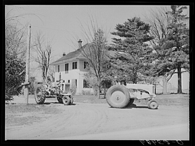 Father and son driving tractors out of the farmyard to a piece of land a mile down the highway where they will disc and plow. Grundy County, Iowa