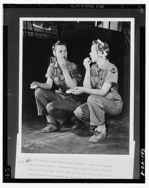 Feminine vanity still demands attention, even in the nation's busy aircraft factories. At Cessna Aircraft Company's plant in Wichita, Kansas, Miss Mina Weber takes a quick time out for facial repair, using a gleaming sheet of aluminum in the stock room as a mirror