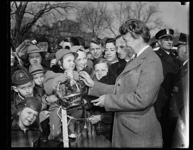 FIRST LADY WELCOMES FIRST OF EASTER EGG ROLLERS. WASHINGTON, D.C. MARCH 25. TWO-YEAR-OLD MARSHA WILLIAMS, DAUGHTER OF CAPT. HERBERT WILLIAMS, U.S. MARINE CORPS AND MRS. WILLIAMS, IS GREETED BY MRS. ROOSEVELT AS SHE ARRIVED TO ROLL HER EASTER EGGS ON THE SOUTH LAWN OF THE WHITE HOUSE TODAY. BECAUSE OF THE COLD WEATHER THE CROWD WAS THE SMALLEST IN 15 YEARS TO ATTEND THE TRADITIONAL FESTIVITIES. MRS. WILLIAMS IS SHOWN ON DAUGHTER'S LEFT
