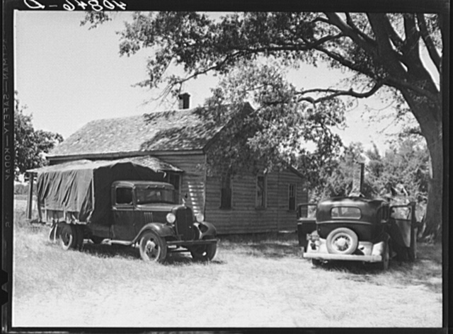 Florida migrants' truck and car outside of farmhouse that houses thirty-seven of them. Old Trap, North Carolina