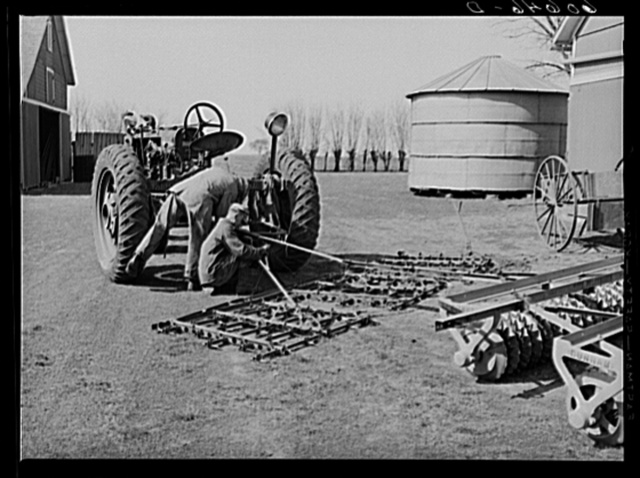Fred Coulter's hired men attaching spike tooth harrow to tractor. Grundy County, Iowa