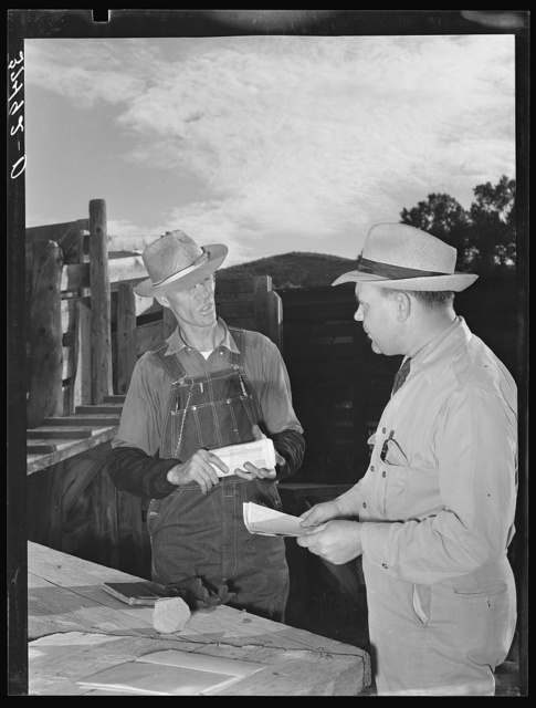 Freight train conductor talking to railroad man who was in charge of shipping livestock. Cimarron, Colorado
