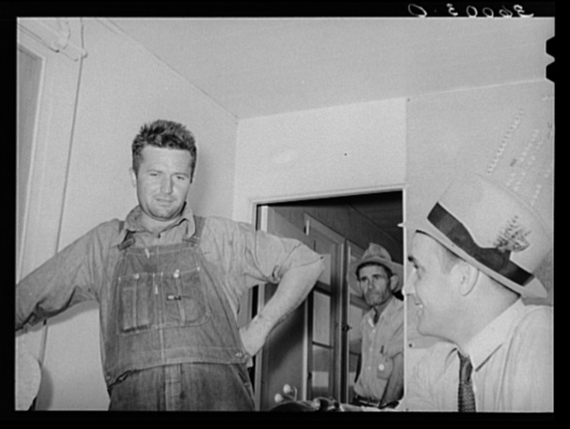 FSA (Farm Security Administration) regional official interviewing man who is interested in living in one of the permanent agricultural laborers' homes at the Aqua Fria migratory labor camp. Arizona