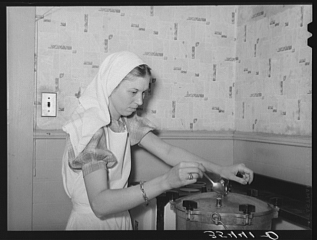 FSA (Farm Security Administration) supervisor giving a demonstration of pressure canning before a group of FSA officials at a district meeting. She is letting off steam from the pressure cooker by opening the steam cock with a spoon. San Angelo, Texas