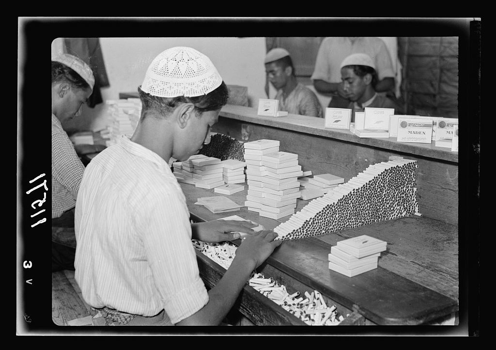 """Galilee trip. Nazareth, the Arab Cigarette & Tobacco Co. Ltd. """"Tatli-Sert"""" Cigarette Factory. Cigarettes being packed into boxes by hand, close up"""