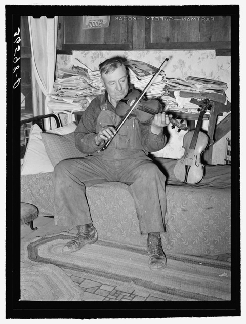 George Hutton, farmer from Maud, Oklahoma, playing his violin which he made. Pie Town, New Mexico