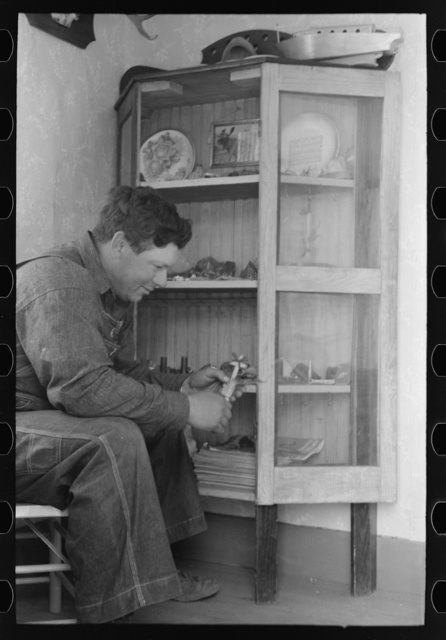George Hutton, Jr. examines fetish used in Indian cermonies. He has a collection of rocks, curios, and Indian relics which is highly prized by the entire family. Pie Town, New Mexico