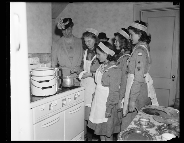 GIRL SCOUTS PREPARE LUNCHEON UNDER WATCHFUL EYES OF MRS. ROOSEVELT. WASHINGTON, D.C. APRIL 30. ARRIVING EARLY AT THE GIRL SCOUTS LITTLE HOUSE WHERE SHE WAS HONOR GUEST AT A LUNCHEON TODAY, MRS. ROOSEVELT WATCHED THE YOUNGSTERS PREPARE THE FOOD THEY LATER SERVED AT THE MEAL. THE FIRST LADY'S VISIT HIGHLIGHTED GIRL SCOUT PARTICIPATION THROUGHTOUT THE COUNTRY IN THE OBSERVANCE OF NATIONAL BETTER HOMES WEEK. SHOWN WITH MRS. ROOSEVELT, L TO R: SARAH DONALDSON; MARIAN FAEL; VIRGINIA STEELE; AND BETTY ROSSER