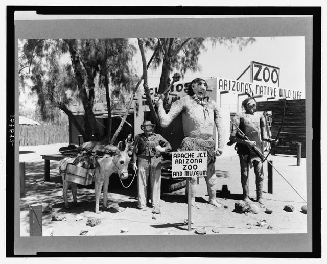 Group of figures made of papier mache which attract passing tourists at Apache Junction, Arizona. These three figures were made to represent three stages in the development of the state, the prehistoric man, the Indian and the prospector