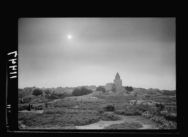 Halhul village at kilom[eter] 30 on Hebron road. Threshing floors of Halhul showing sun through a haze with Neby Yunis shrine