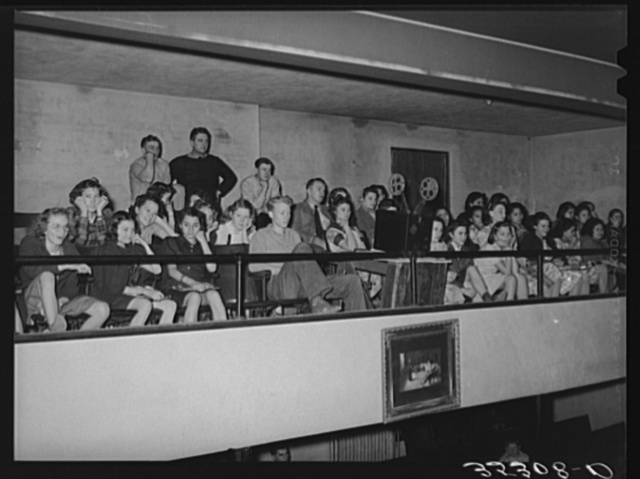 High school students in balcony of school auditorium watching moving picture which was part of the Americanization program. Eufaula, Oklahoma