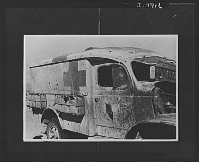 Hospital units at work. A plainly marked ambulance which was attacked by Axis forces. Note the bullet holes