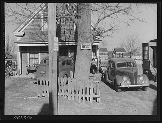 "House on Winter Street, Quincy, Massachusetts. Because of lack of parking facilities, people living in the vicinity of the shipyards are renting car space in their backyards and the lots around their houses for ""fifty cents a week."""