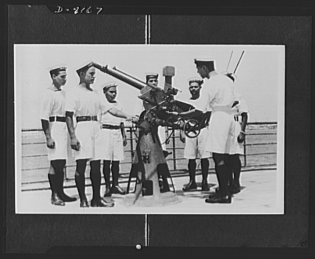 Indian troops in East Africa. A series of photos taken on board a vessel of the Royal Indian Navy on active service in Eastern waters. Captured Italian equipment proves that they have been in action. Gunnery instruction is given to the men with a captured Italian Breda gun