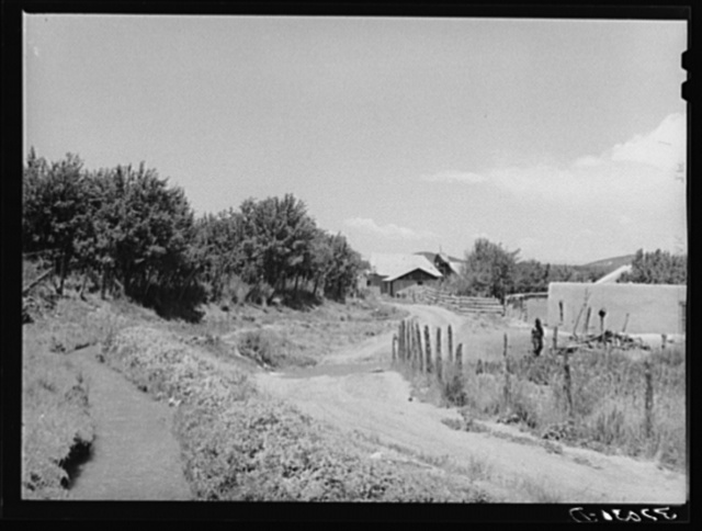 Irrigation ditch flows across road at entrance to Chamisal, New Mexico