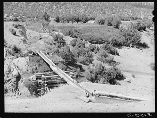 Irrigation water crossing ditch in hollowed out log. Trampas, New Mexico