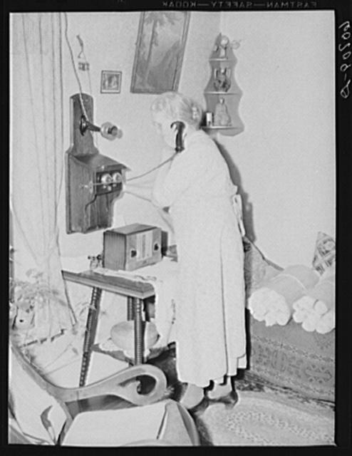 Lady signaling operator on old style telephone. Scranton, Iowa