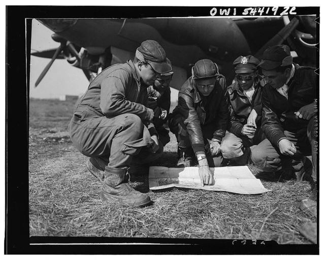 "Last minute check-up. Just before taking off, a bomber crew reviews details of its mission, the target of which is a major German rail center in central Italy. Before ""Operation Strangle"" went into effect, German forces in Italy were well-supplied since the Italian rail system was one of the best in Europe. Thus, first objectives of Allied bombers were key rail lines."