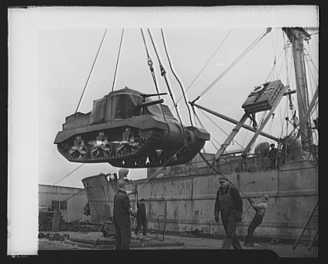 """Lend-lease in action. American M-3 tanks, """"General Grants,"""" are in action in Africa and are preparing for battle in Australia. The picture shows an M-3 tank, lend-leased to the United Nations, being hoisted aboard a cargo vessel at an unnamed American port"""