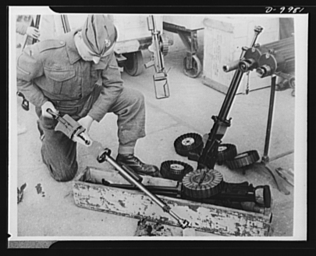 Lend-Lease to Britain. An American-made machine gun is unpacked and assembled at an ordnance depot in England, having been shipped from the United States