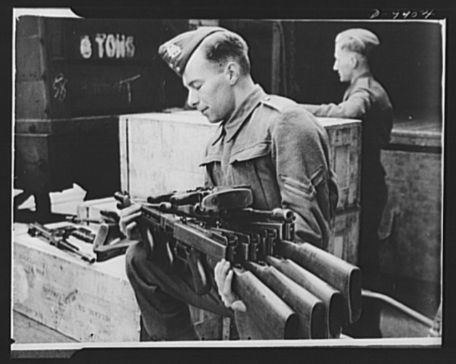 Lend-Lease to Britain. Tommy-guns arriving in England from the United States under lend-lease are unpacked and checked by an ordnance corporal. The guns arrived complete, ready to be fired