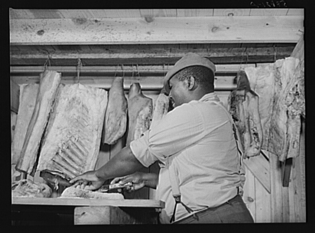 Lewis Wiggins cutting off a slice of homecured ham in his smokehouse. La Delta Project, Thomastown, Louisiana