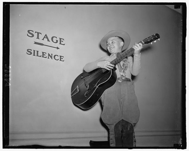 Little Billy Hill, backstage, does not believe in signs, as he rehearses just before going on to do his bit. His specialty lies in folk tunes from Arkansas