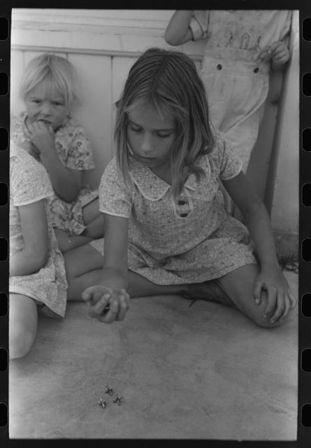 Little girl playing jacks at the Casa Grande Valley Farms, Pinal County, Arizona