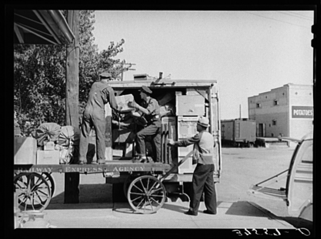 Loading express packages into D. & R.G.W. truck which takes them to points on the narrow gauge railroad where passengers and express service is not otherwise available. Montrose, Colorado