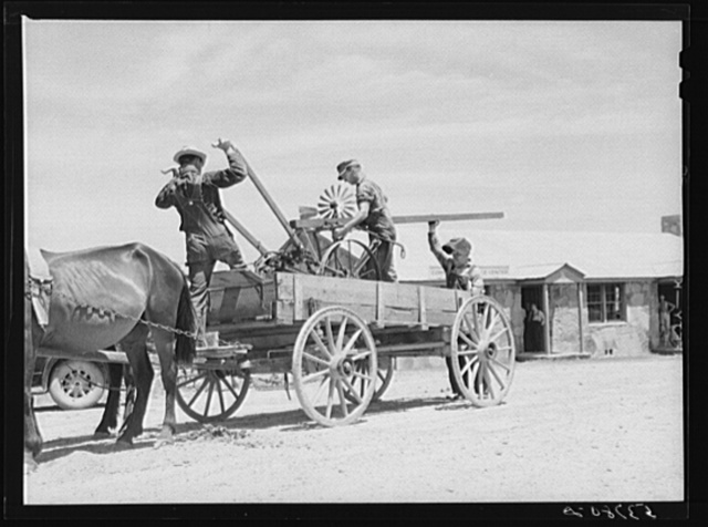 Loading farm machinery onto wagon after repairing at community service center. Faulkner County, Centerville, Arkansas (see general caption)