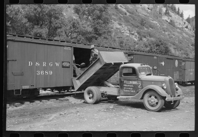 Loading gold ore concentrate into freight cars of narrow gauge railroad, Ouray, Colorado