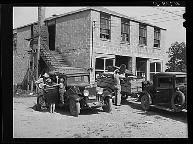 Loading household goods into cars and trailer. Two families getting ready to move on in search of work picking fruit. Berrien County, Michigan