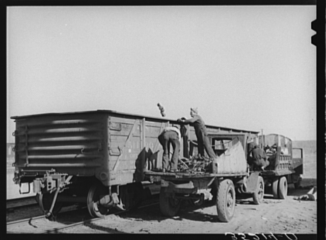 Loading scrap iron into freight cars. Oklahoma City, Oklahoma. Proximity of oil fields accounts for the large amount of scrap iron collected and shipped out of Oklahoma City