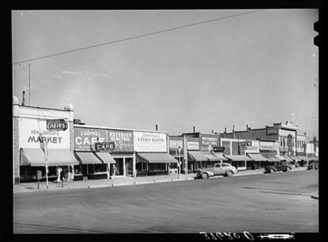 Main street of Brigham, Utah. In the small shopping centers in the Mormon communities the business establishments are likely to be many small ones rather than one large company dominating