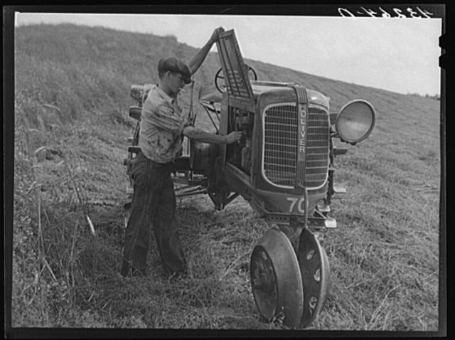 Making adjustments on tractor. Farm near Rockville, Maryland