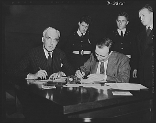 McNutt registers for draft. Paul V. McNutt, (FSA) Federal Security Administrator and recently-appointed chairman of the Manpower Commission, registers under the Selective Service Act at the Woodrow Wilson High School, Washington, D.C., April 25. Assisting him is Dr. William A. Killgore, draft registrar