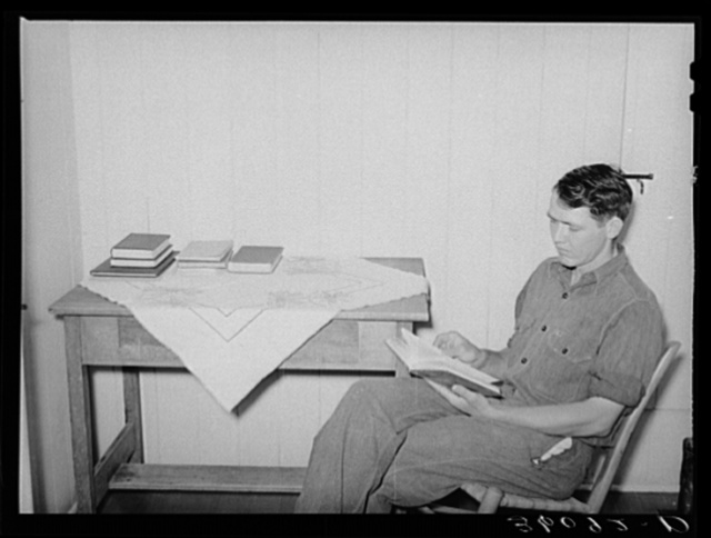 Member of the Arizona part-time farms, Chandler Unit, in bedroom of his apartment on the project studying for civil service examination in poultry culture. Maricopa County, Arizona