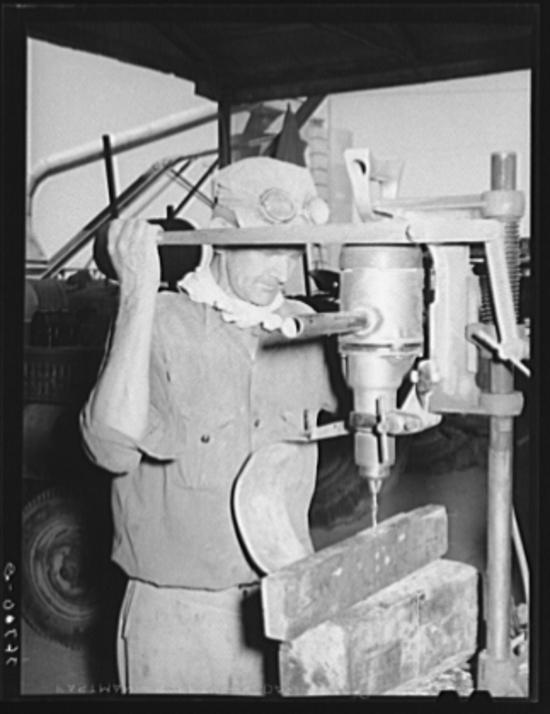 Member of the Casa Grande Valley Farms using an electric drill in making repairs for hay chopper. Pinal County, Arizona