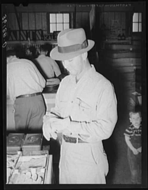 Member of the United Producers and Consumers Cooperative of Phoenix, Arizona, trying on a pair of gloves