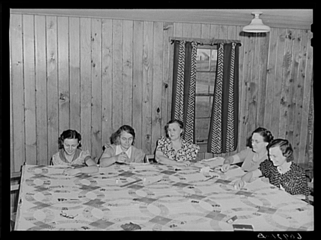 Members of the women's club making quilt. Granger Homesteads, Iowa
