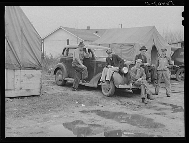 """Men on car by tents. Construction workers in front of tents. Names: William Allen Jones, Fort Benning, Paul Knight, Fort Benning, J.F. Goza, C.D. Brownlee and B.I. Juhan. For space only in W.T. Mullis' backyard they pay two dollars a week. Two of them are now working at Fort Benning and others the Williams Construction Company, building foundations for new barracks, got laid off couple of weeks ago for indefinite time. They all came from Stone Mountain, Atlanta, Georgia, where they worked on WPA (Work Projects Administration). Some have been here one month. One said """"There's something crooked in this here job--some men have worked every day seven days a week and others get no work at all. It's a dirty shame and the government ought to know about these conditions and see what goes on. It's awful bad."""""""