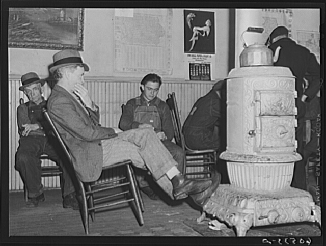 Men sitting around stove in lobby of thirty-five cents a night hotel. Dubuque, Iowa