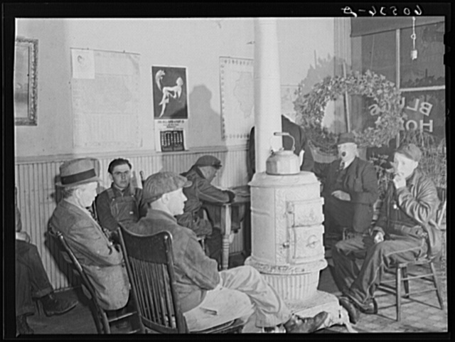 Men sitting around the stove in lobby of thirty-five cents a night hotel. Many of these men are transient men (farm laborers) who quarter here during the winter. Dubuque, Iowa